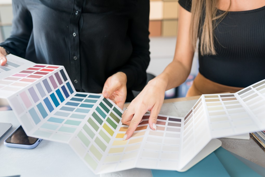 A couple planning their home renovation by choosing paint colours